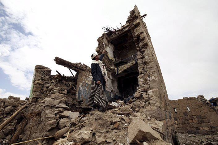 A man points up at a house that was damaged during an airstrike carried out by the Saudi-led coalition in Faj Attan village, Sanaa, Yemen May 7, 2015.