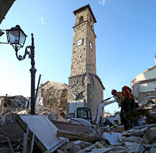 Rescuers walk past the bell tower with the clock showing the time of the earthquake in Amatrice, central Italy, August 24, 2016