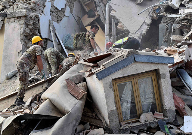 Rescuers work at a collapsed building following an earthquake in Amatrice, central Italy, August 24, 2016