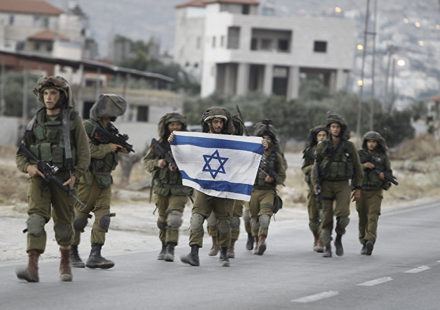 Israeli soldiers holding their national flag patrol a street in the West Bank village of Beit Furik, southeast of Nablus, early on June 20, 2014.