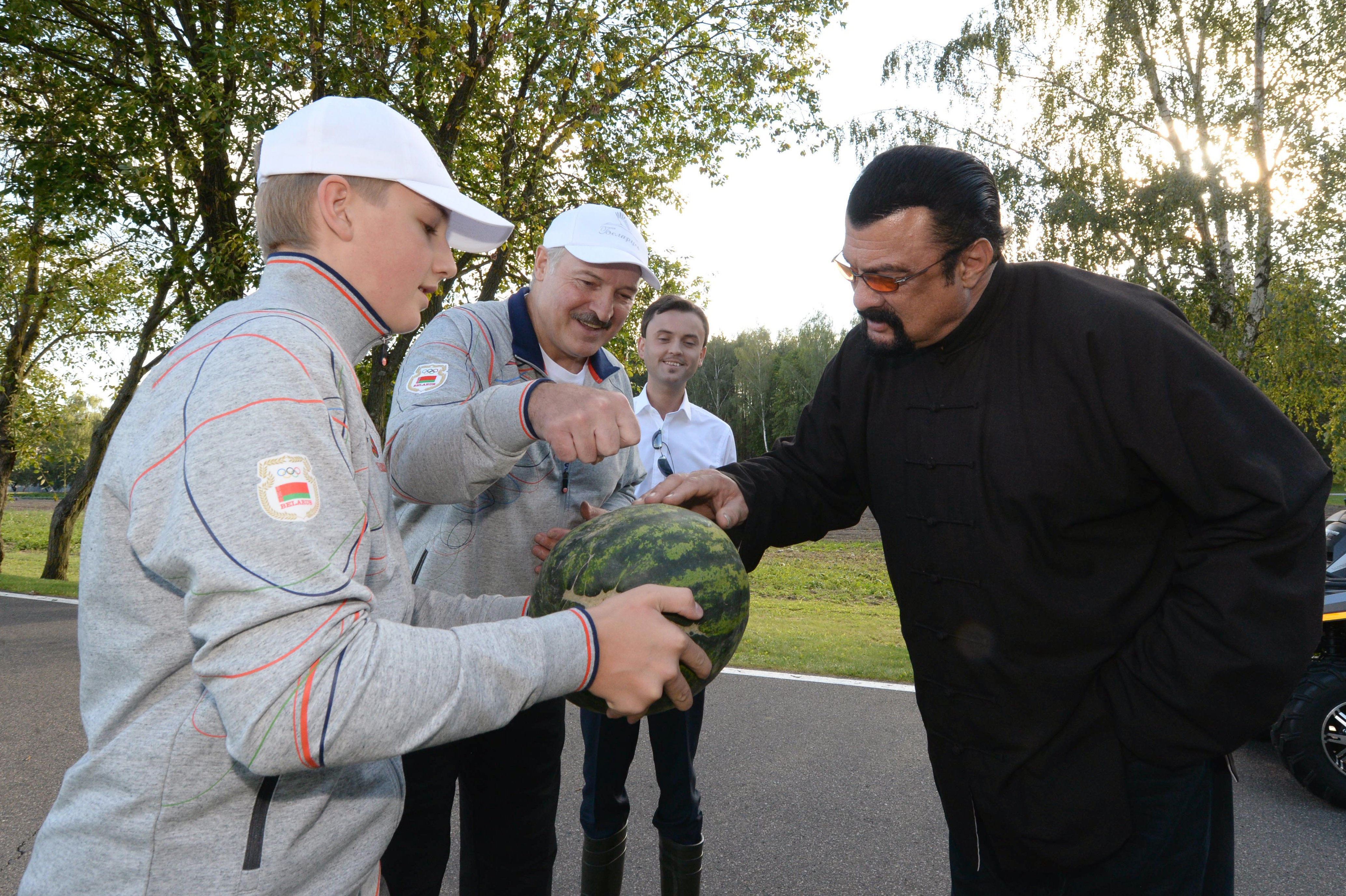 Belarus President Alexander Lukashenko (C) and his son Nikolai (L) hand over a watermelon to US actor Steven Seagal (R) who has been recenlty granted Serbian citizenship, during their meeting at their residence of Drozdy, outside Minsk