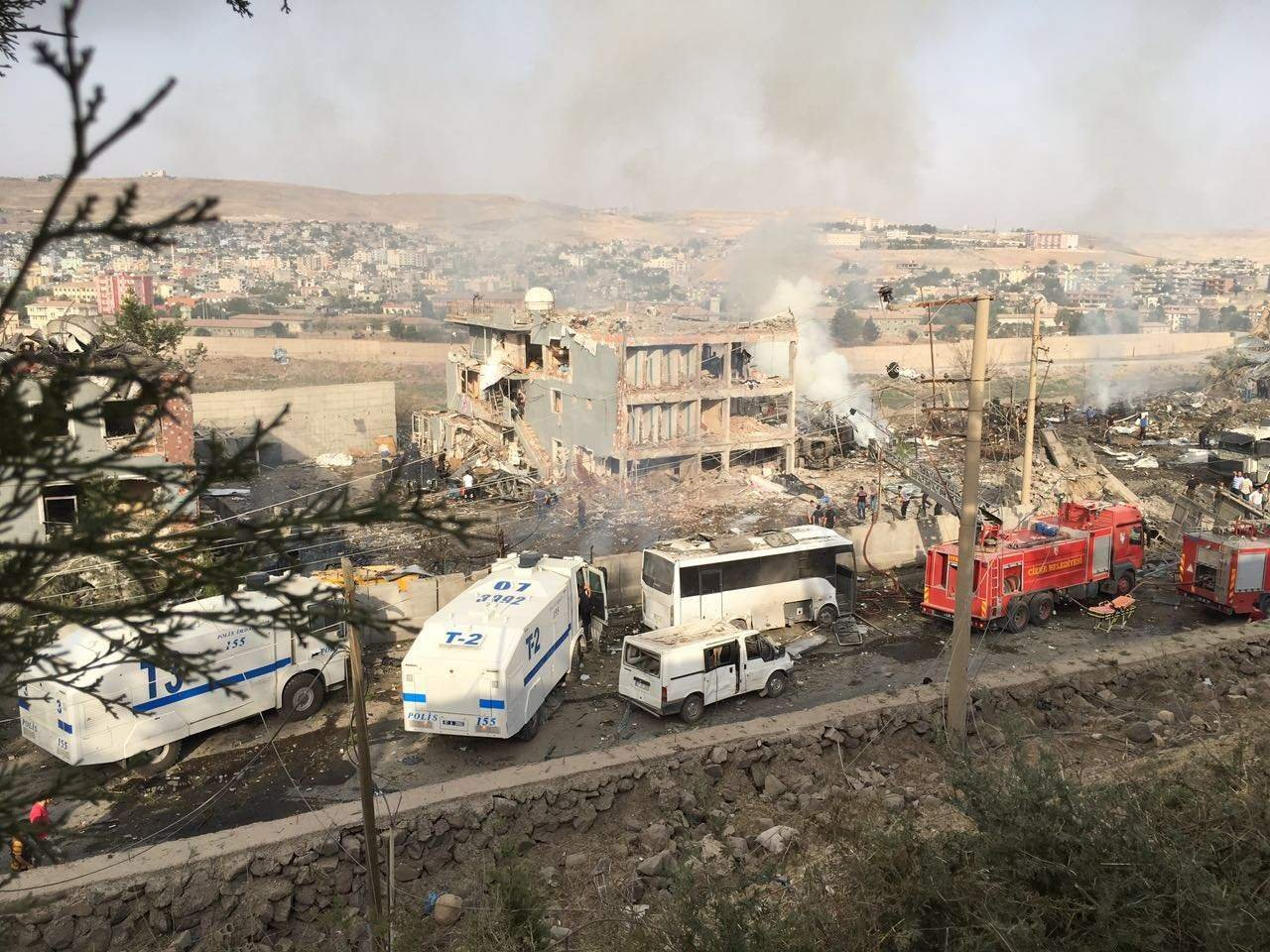 Turkish police and firefighters are parked near a damaged police headquarters in Cizre, southeastern Turkey