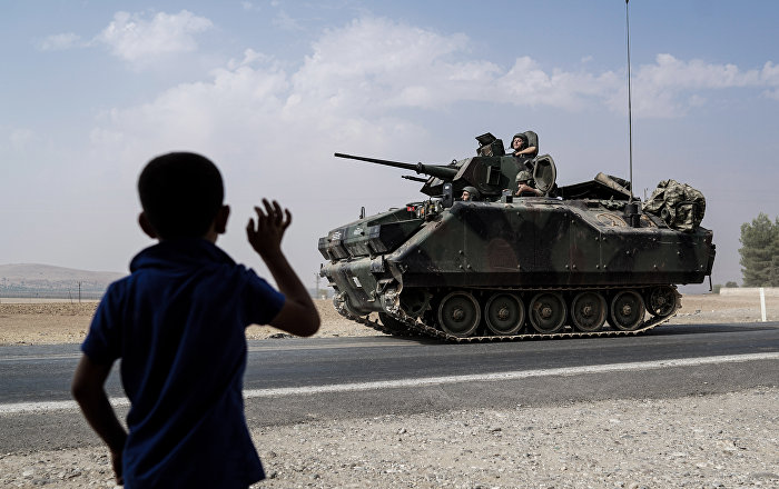A child waves toward Turkish troops heading to the Syrian border, in Karkamis, Turkey, Friday, Aug. 26, 2016