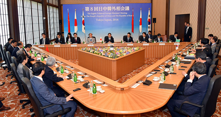 Japanese Foreign Minister Fumio Kishida, center in the background, makes opening remark during a trilateral meeting in Tokyo, Wednesday, Aug. 24, 2016