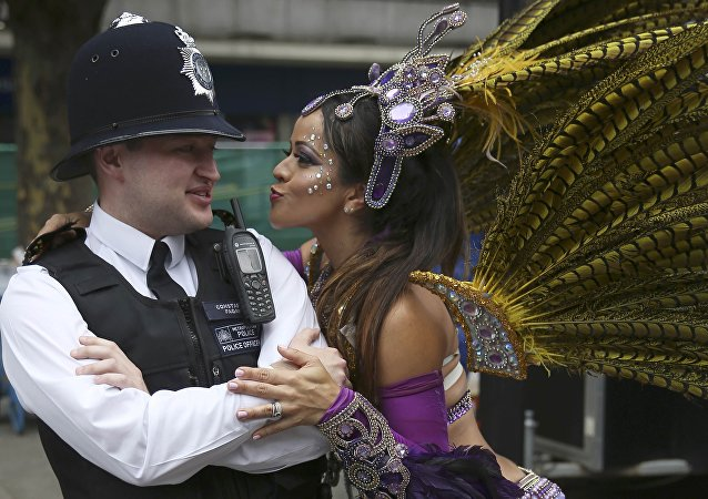 A performer dances with police during the Notting Hill Carnival in London, Britain August 29, 2016