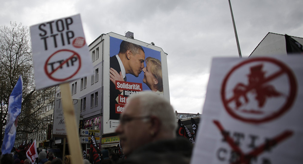 A man holds a poster with the slogan Stop TTIP as he passes a huge poster against TTIP with President Barack Obama and Chancellor Angela Merkel during a protest of thousands of demonstrators against the planned Transatlantic Trade and Investment Partnership, TTIP, and the Comprehensive Economic and Trade Agreement, CETA, ahead of the visit of United States President Barack Obama in Hannover, Germany, Saturday, April 23, 2016