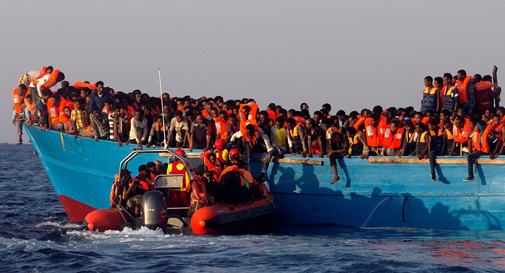 A rescue boat of the Spanish NGO Proactiva approaches a wooden vessel loaded with migrants from Eritrea off the Libyan coast in Mediterranean Sea, 29 August 2016