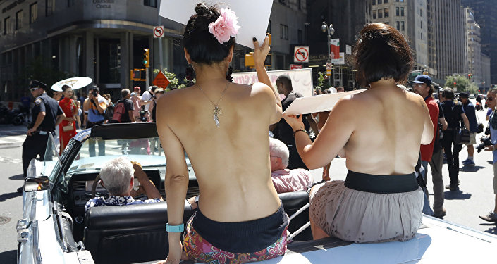 Participants ride in a convertible through midtown Manhattan in the Go Topless Pride Parade, Sunday, Aug. 28, 2016, in New York