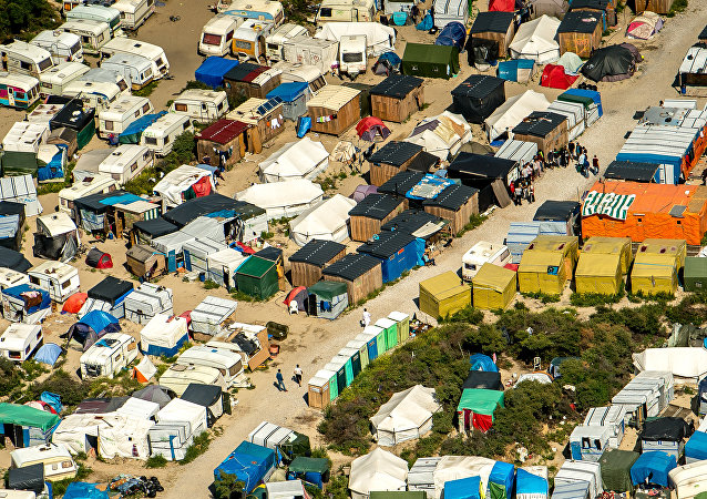 This aerial view taken on August 16, 2016, in Calais, northern France shows tents and people walking in the jungle camp where over 9000 migrants live according to different NGOs