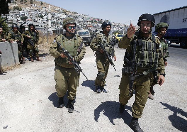 Israeli soldiers are seen at the site of a stabbing attack by a Palestinian man next to the entrance of the al-Arub refugee camp near the city of Hebron in the Israeli-occupied West Bank on July 18, 2016