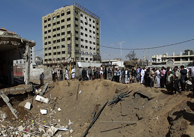 Yemenis gather around a crater caused by a Saudi-led airstrike that targeted a building in the centre of the capital Sanaa (File)