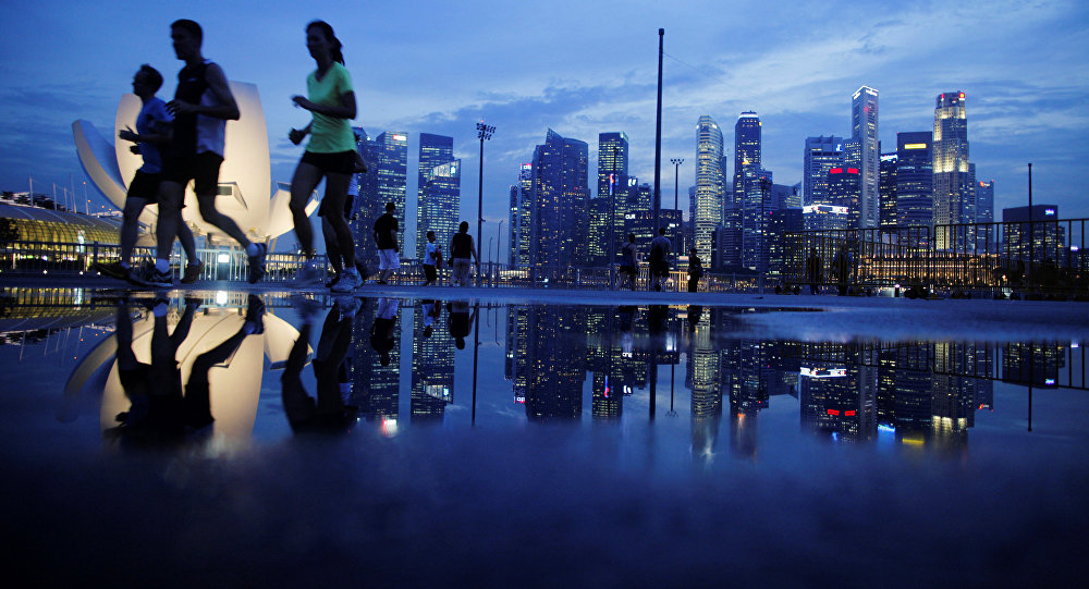 Joggers run past as the skyline of Singapore's financial district is seen in the background
