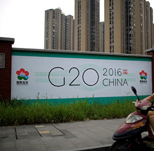 A man rides an electronic bike past a billboard for G20 summit in Hangzhou, Zhejiang province, China