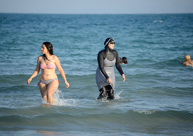 Tunisian women, one (R) wearing a burkini, a full-body swimsuit designed for Muslim women, swim at Ghar El Melh beach near Bizerte, north-east of the capital Tunis