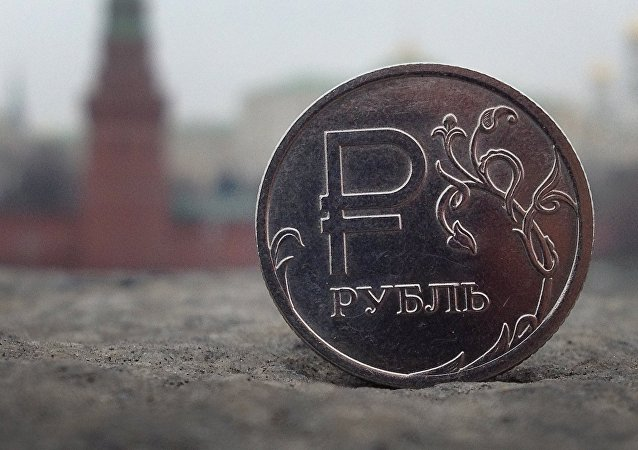 A Russian ruble coin is pictured in front of the Kremlin in in central Moscow, on November 6, 2014