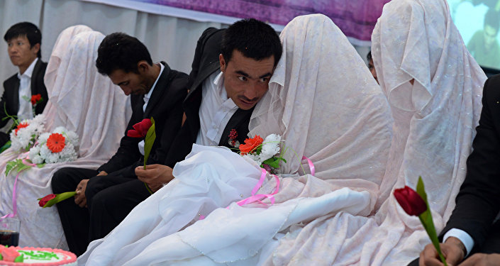 In this photograph taken on October 10, 2014, an Afghan groom (C) talks with his bride during a mass wedding ceremony in which one hundred couples were married on the outskirts of Kabul
