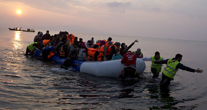 In this Sunday, March 20, 2016 file photo, volunteers help migrants and refugees on a dingy as they arrive at the shore of the northeastern Greek island of Lesbos, after crossing the Aegean sea from Turkey.