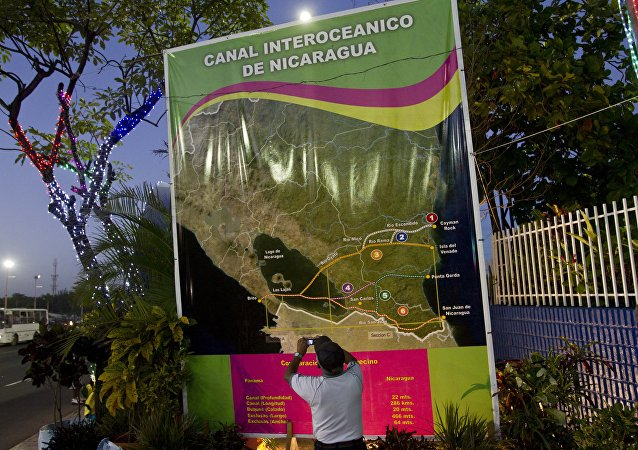 In this Dec. 4, 2013 photo, Oscar Torres, a 62-year-old retired construction worker takes photos of a banner showing a map of Nicaragua with possible routes of the Inter-Oceanic canal in Managua, Nicaragua