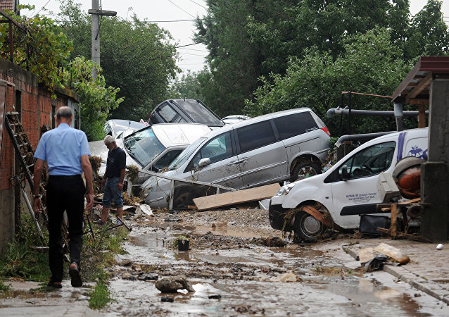 People walk through a street where cars have piled due to overnight flooding, after storms in the village of Stajkovci, just east of Skopje, Macedonia, Sunday, Aug. 7, 2016.