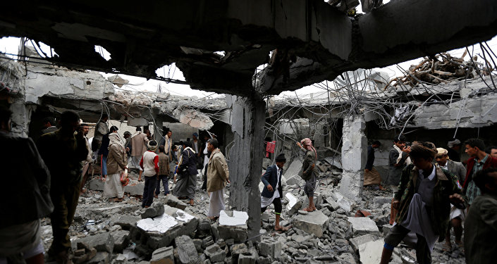 People gather at a building destroyed by Saudi-led air strikes in the northwestern city of Amran, Yemen September 8, 2016