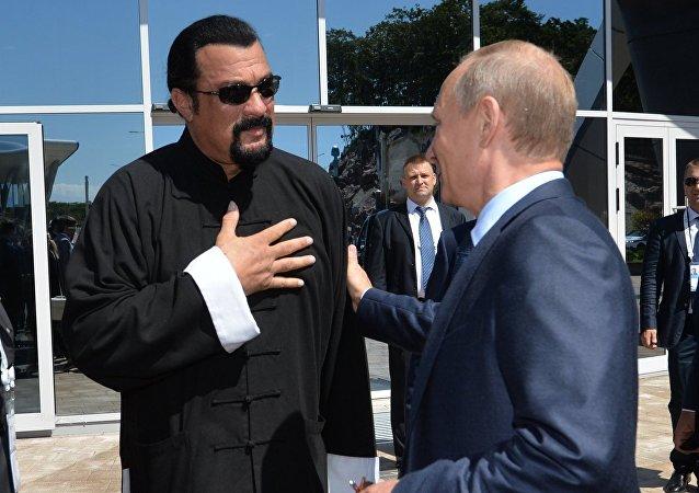 Russian President Vladimir Putin, right, visits the oceanarium on Russky Island, Vladivostok. Left: US actor Steven Seagal