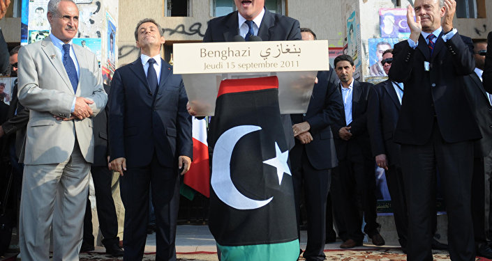 Britain's Prime Minister David Cameron addresses the gathering from a podium decked with the National Transitional Council's (NTC) adopted flag in Benghazi on September 15, 2011.