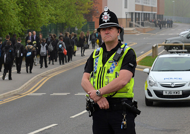 A police officer stands guard as pupils (L) arrive for school at Corpus Christi Catholic College in Leeds, northern England on April 29, 2014