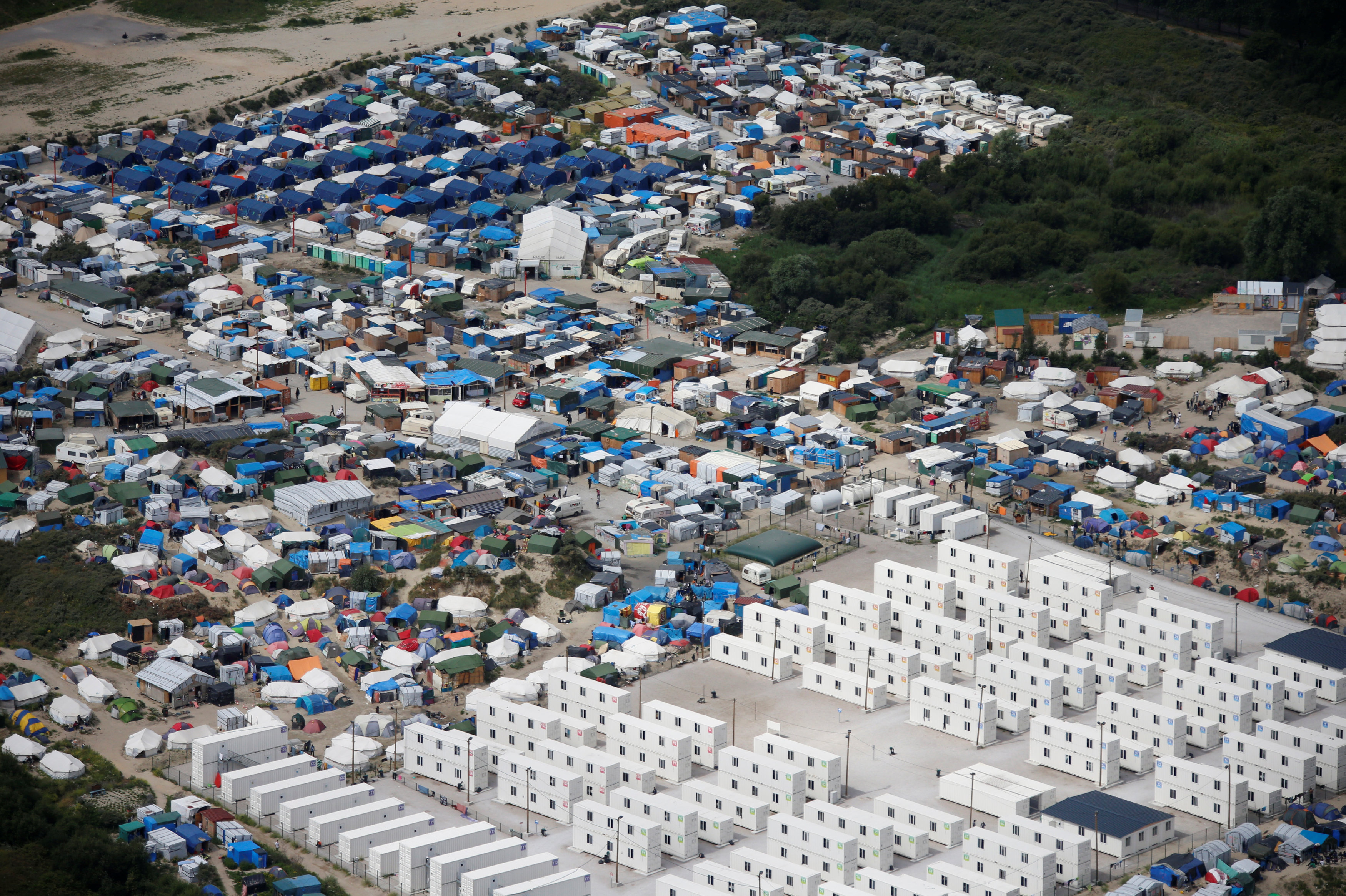 Aerial view of a makeshift camp as containers (front) are put into place to house migrants living in what is known as the Jungle, a sprawling camp in Calais, France, August 14, 2016