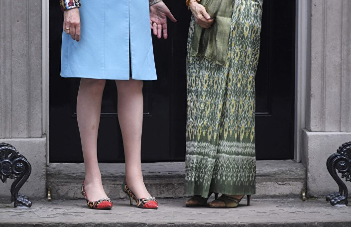 Britain's Prime Minister Theresa May (L) greets Myanmar's First and incumbent State Counsellor and Leader of the National League for Democracy Aung San Suu Kyi outside 10 Downing Street, in London September 13, 2016.