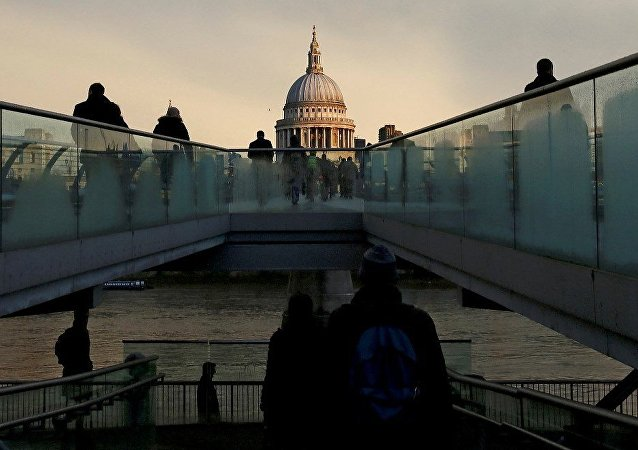 City workers walk towards St Paul's Cathedral as they cross the Millennium footbridge during sunrise in central London, Britain, January 14, 2016.