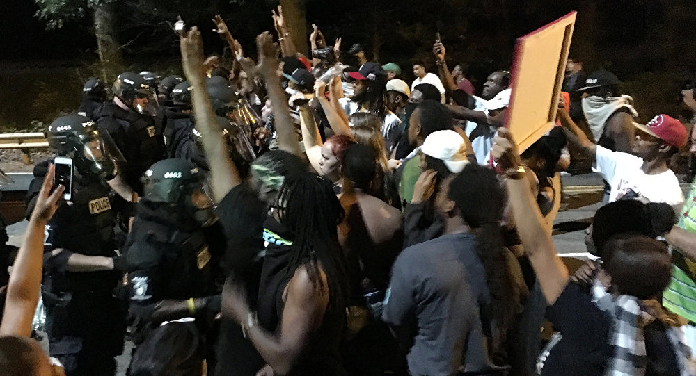 Protestors demonstrate in front of police officers wearing riot gear after police fatally shot Keith Lamont Scott in the parking lot of an apartment complex in Charlotte, North Carolina, U.S. September 20, 2016