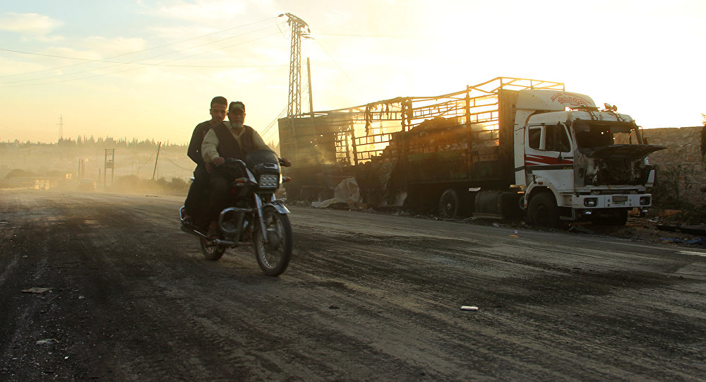 Men drive a motorcycle near a damaged aid truck after an airstrike on the rebel held Urm al-Kubra town, western Aleppo city, Syria September 20, 2016
