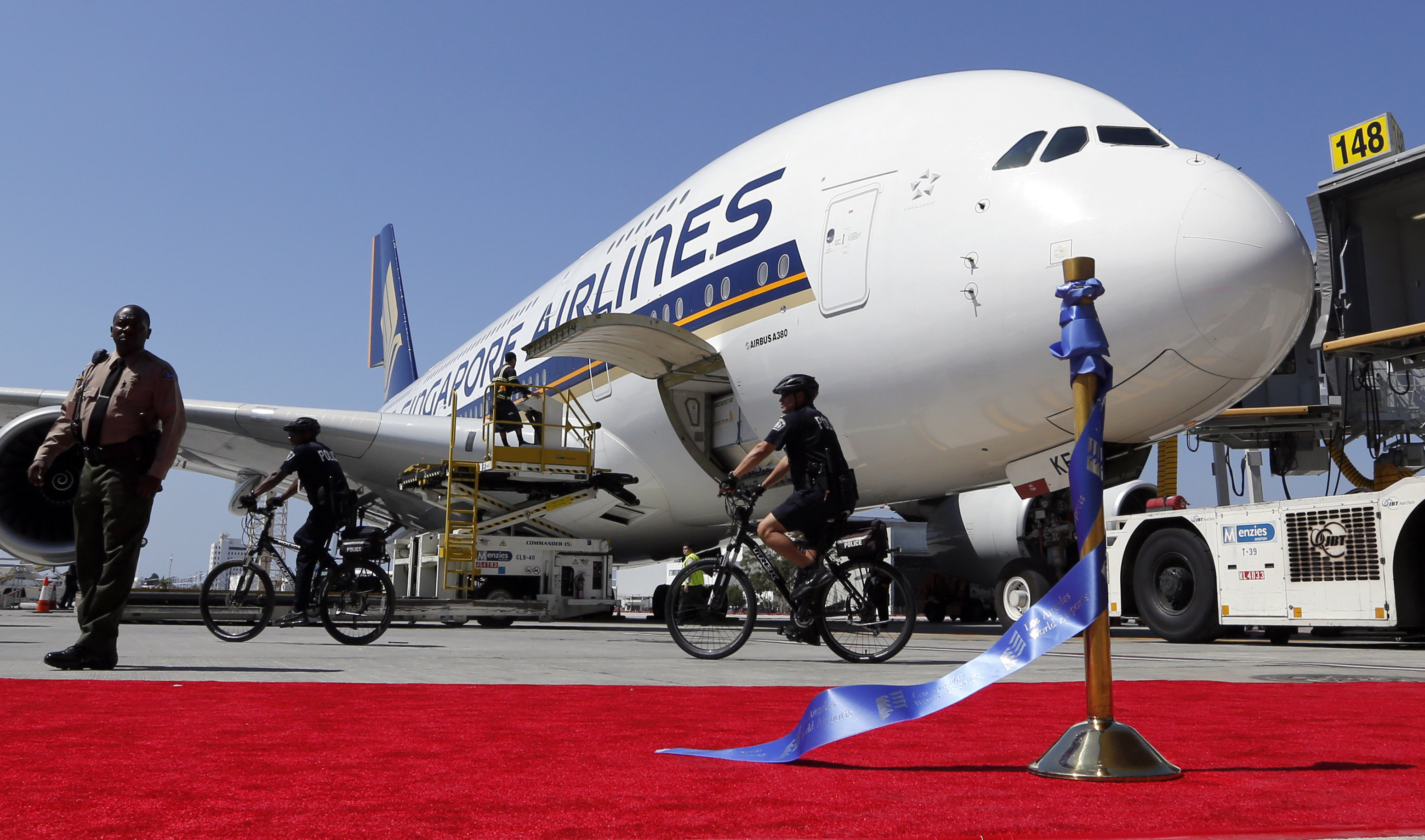 A Singapore Airlines Airbus 380 is parked behind a red carpet and stantion holding the ceremonial ribbon that was cut at the grand opening of the Tom Bradley International Terminal at Los Angeles International Airport. File photo