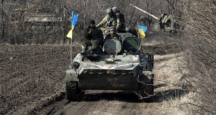 Ukrainian servicemen ride atop armored vehicle with a canon in tow and Ukrainian flags