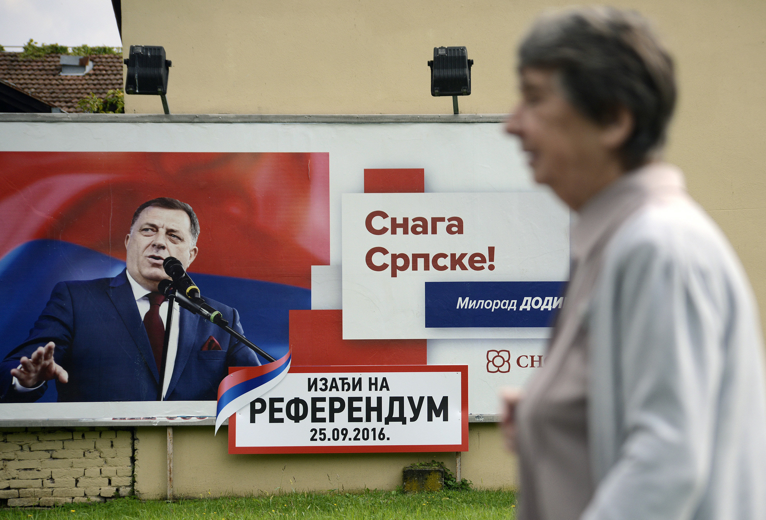 In this photo taken on Wednesday, Sep. 21, 2016. Bosnian woman passes by poster for Sundays referendum in the Bosnian town of Banja Luka, 240 kms (150 miles) northwest of the Bosnian capital Sarajevo , Bosnia