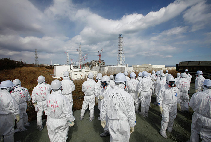 Members of the media wearing protective suits and masks report as they are escorted by TEPCO employees at Tokyo Electric Power Co. (TEPCO)'s tsunami-crippled Fukushima Daiichi nuclear power plant in Okuma, Fukushima prefecture on February 20, 2012.