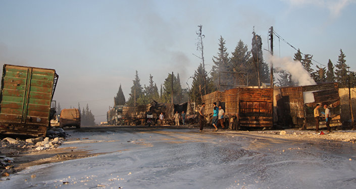 Syrians gather near damaged trucks carrying aid on the side of the road in the town of Orum al-Kubra on the western outskirts of the northern Syrian city of Aleppo on September 20, 2016, the morning after a convoy delivering aid was hit by a deadly air strike