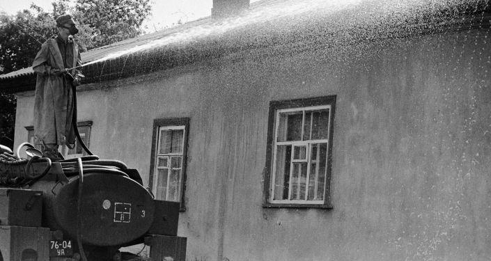 A member of decontamination team sprays a house in Chernobyl.