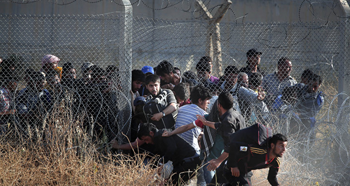 In this file photo taken from the Turkish side of the border between Turkey and Syria, in Akcakale, Sanliurfa province, southeastern Turkey, Syrian refugees burst into Turkey after breaking the border fence