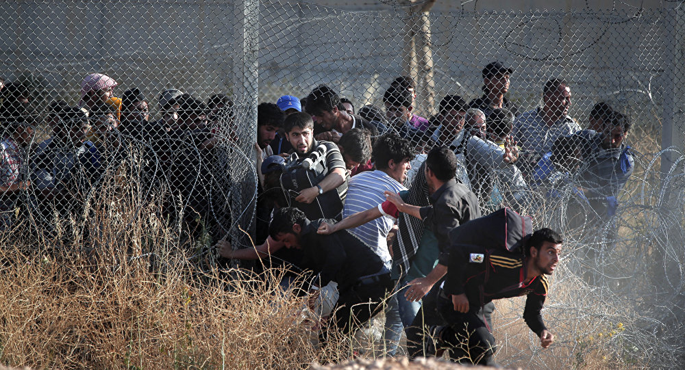 File photo taken from the Turkish side of the border between Turkey and Syria, in Akcakale, Sanliurfa province, southeastern Turkey, Syrian refugees burst into Turkey after breaking the border fence and crossing from Syria cross into Turkey