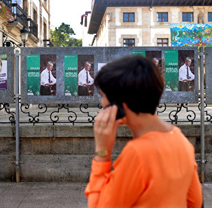 A woman walks past election posters for Basque nationalist Party (PNV) candidate, Inigo Urkullu, in the Basque town of Guernica, northern Spain, September 21, 2016.
