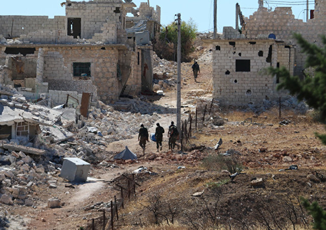 Syrian government forces walk amidst debris in the largely deserted Palestinian refugee camp of Handarat, north of Aleppo, on September 24, 2016