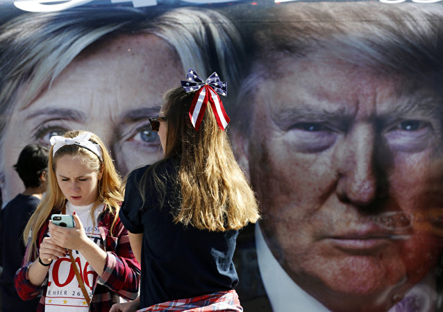 People pause near a bus adorned with large photos of candidates Hillary Clinton and Donald Trump before the presidential debate.