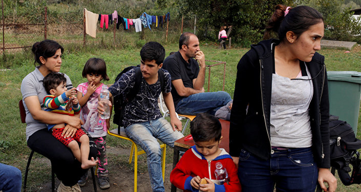 A group of people wait to get accommodation at the entrance of a camp for refugees and migrants in the Belgrade suburb of Krnjaca, Serbia, September 21, 2016.