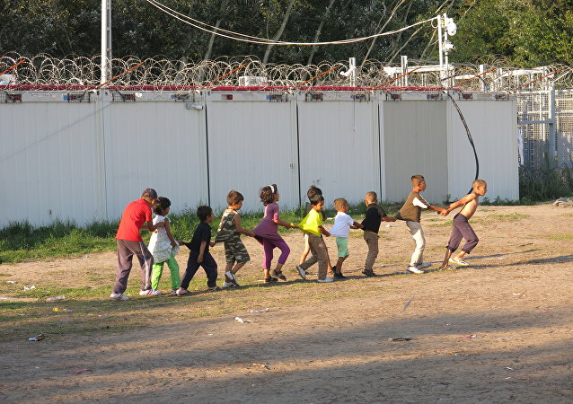 Boarders in Hungary stand tall as children play and attempt to try and live a normal life in the camp.