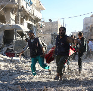 Syrian volunteers carry an injured person on a stretcher following Syrian government forces airstrikes on the rebel held neighbourhood of Heluk in Aleppo, on September 30, 2016