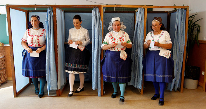Hungarian women wearing traditional costume leave a voting booth at a polling station during a referendum on EU migrant quotas in Veresegyhaz, Hungary, October 2, 2016
