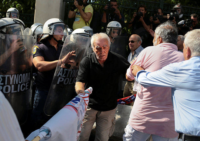 Greek pensioners scuffle with riot police during a demonstration against planned pension cuts, in Athens, Greece