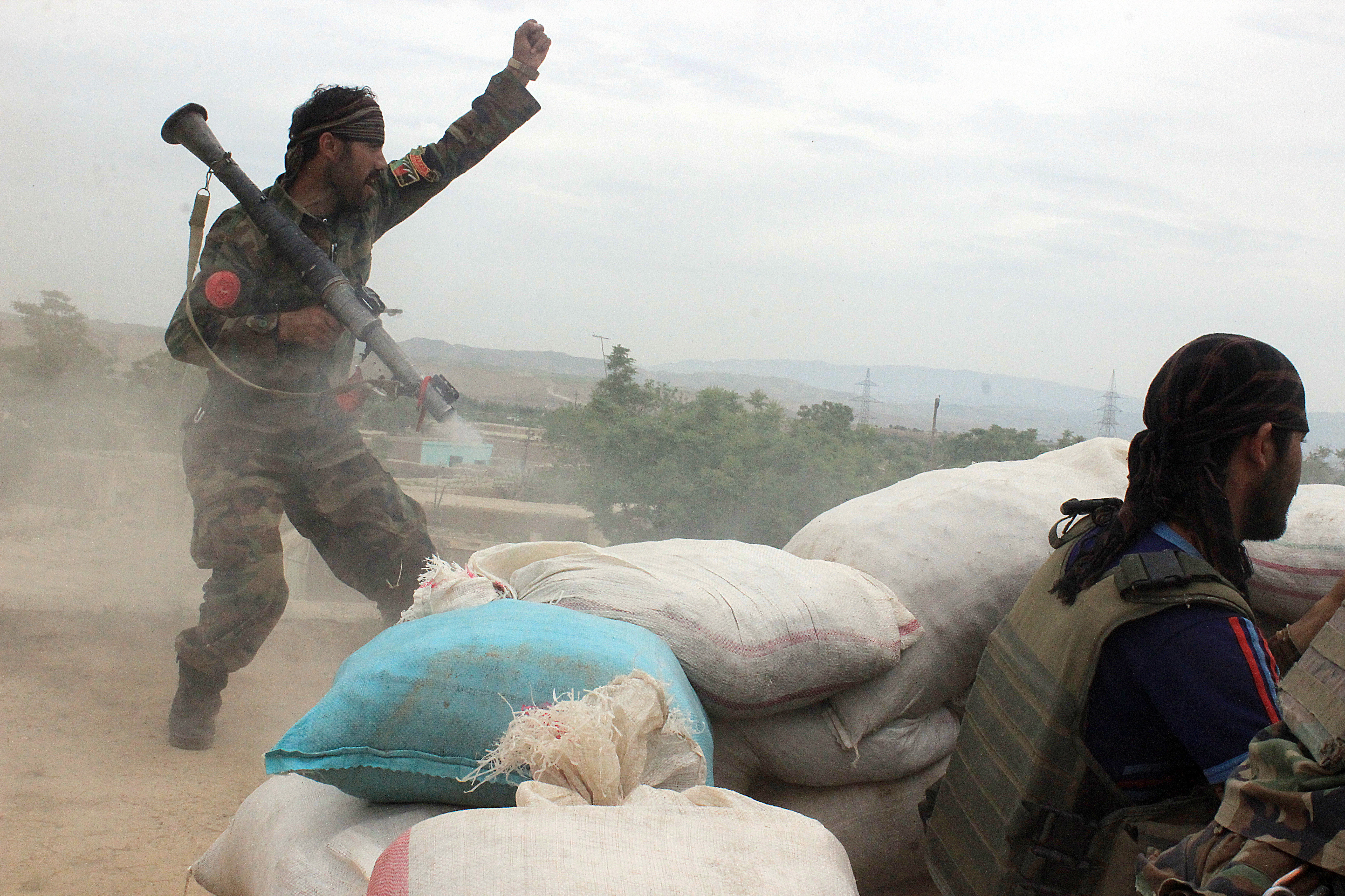 An Afghan National Army soldier, left, shouts against the Taliban, after firing a rocket towards Taliban positions, on the outskirts of Kunduz, northern Afghanistan (File)