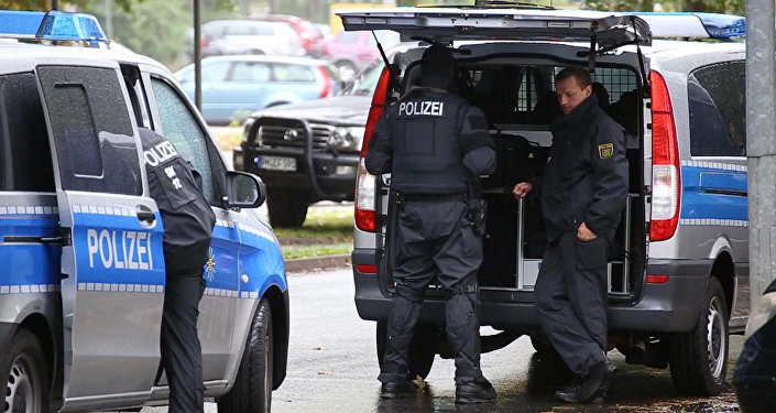In this image taken from Nonstop News video, police officers surround an apartment in the eastern city of Chemnitz, Germany, Saturday Oct. 8, 2016